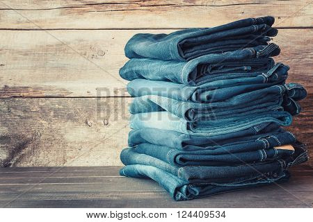 Stacked fashion blue jeans in store on wooden shelf