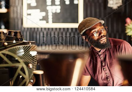 Portrait of a fashionable African man with a hipster style beard, spectacles and cap, sitting in a modern coffee shop and looking away in deep thought, with gentle light falling on his face