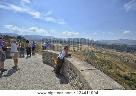 Ronda Spain - September 16 2013: Woman and her dog at the terrace of Ronda