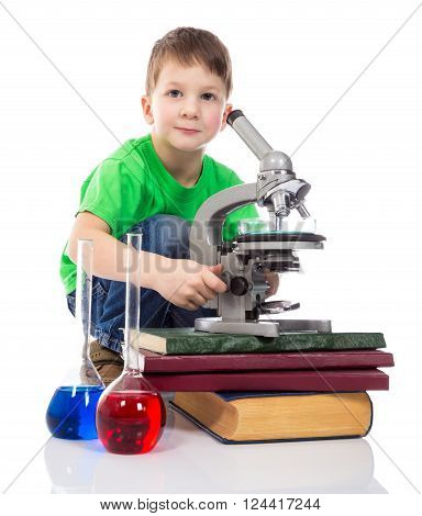 Interested small boy with microscope. Isolated on white background