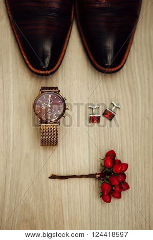 Groom's morning. Wedding accessories in red colors. Cufflinks watch shoes boutonniere.