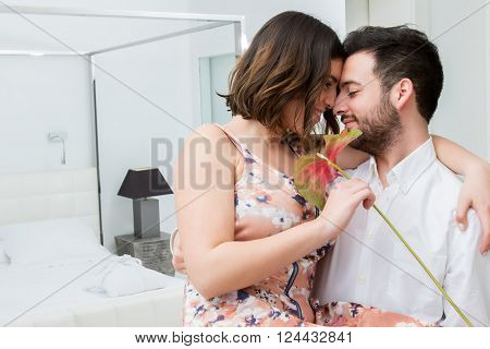 Close up portrait of man holding woman in arms. Couple with red flower in room showing affection.