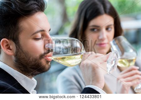 Close up portrait of young man tasting white wine in restaurant next to girlfriend.