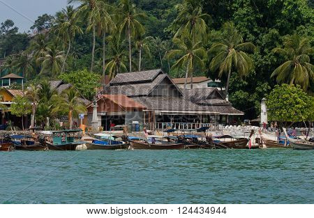PHI PHI DON, THAILAND - MARCH 2: Tropical village with longboats and wooden houses under palm trees on March 2, 2015. Tropical Ko Phi Phi National Park covers about 39000 hectares