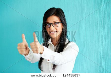 Young Woman Gesturing Ok With Thumbs Up, On A Blue Background