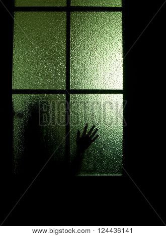 Blurred silhouette of a child behind a glass door in the darkness (symbolizing sadness loneliness horror or fear)