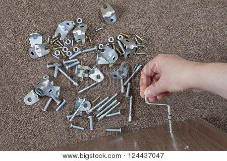 Carpenter assembles furniture at home using hex key.