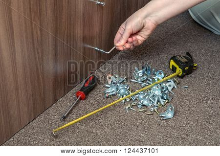 Key furniture screws mans hand screw up wooden board with hex wrench.