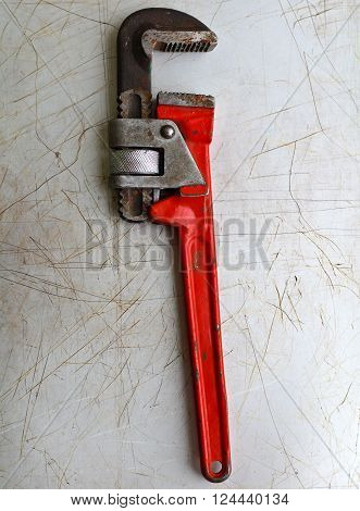 red screw-wrench on a rusty metal background