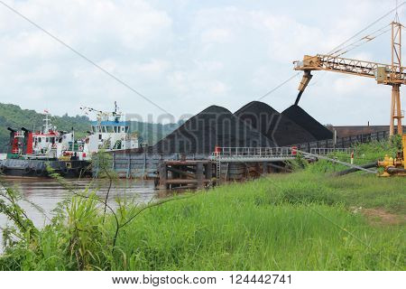 Process loading from conveyor to barges with tug boat