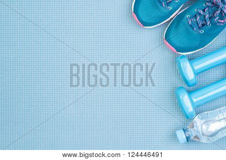 Fitness equipment  on blue background with copy space