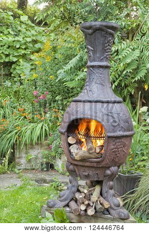 Rustic cast iron wood burning stove Mexican chiminea with flames ready for barbeque in summer cottage flower garden