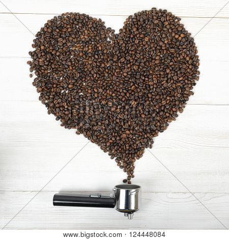 A portafilter handle and a heart shaped rammer with arabica seeds. Composition.
