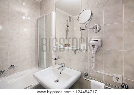 Interior design of a hotel bathroom. Hotel restroom interior design. Washbasins, sink, toilet, shower cabin. Clean public bathroom in hotel, disinfected. Contemporary interior design. Modern bathroom.