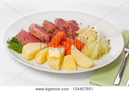 Corned beef dinner with cabbage carrots and baked potatoes on a white plate.