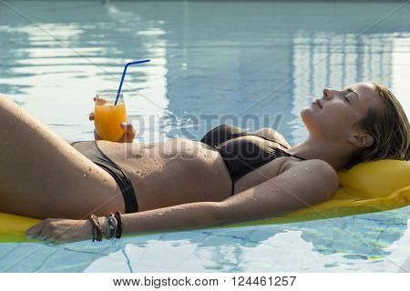 Young attractive blond woman laying down on a floating matress holding a glass of an orange juice