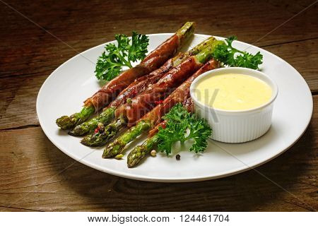 grilled green asparagus wrapped in prosciutto bacon with parsley garnish and hollandaise sauce white plate on a rustic wooden background selected focus narrow depth of field
