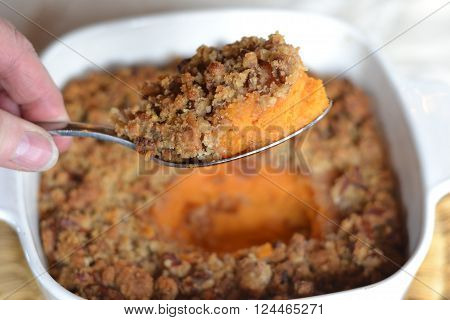 Sweet Potato casserole with crunchy pecan topping; hand holding spoonful of food with casserole dish in background.