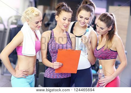 Group of women discussing plan with personal trainer in gym