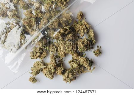Pile of medical cannabis dried buds scattered from nylon package on white background from above
