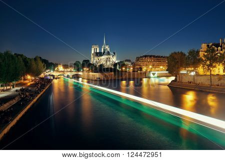 Notre Dame de Paris at dusk over River Seine with boat light trail as the famous city landmark.