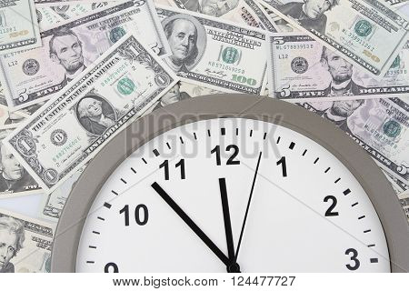 Clock on assorted American banknotes. Time is money idea