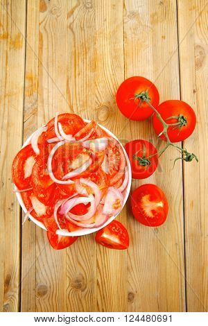 vegetable food : fresh tomato salad with onion in white bowl over wood