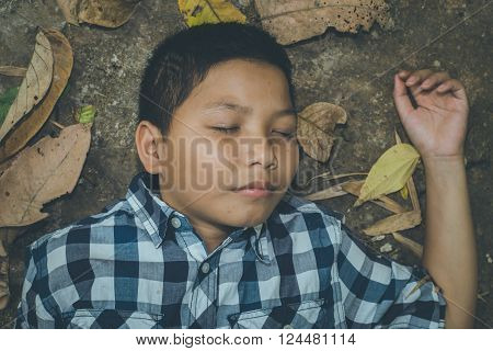 young Asian child lying on the ground after being abused