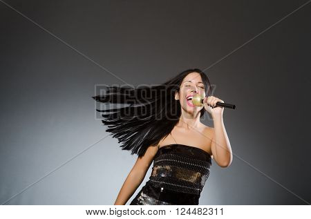 Young woman singing in karaoke club