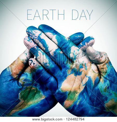 the text earth day and the hands of a young man put together patterned with a world map (furnished by NASA)