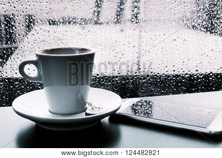 closeup of a cup of coffee and a smartphone on a table while is raining outside