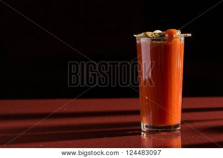 photo of delicious tomato bloody mary cocktail on reflecting glass table with spot light