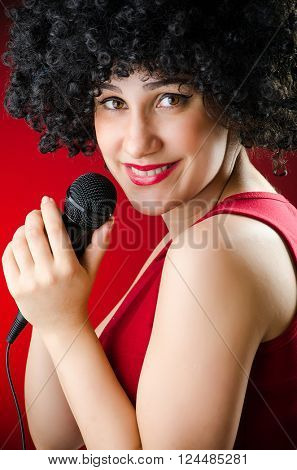 Woman with afro hairstyle singing in karaoke