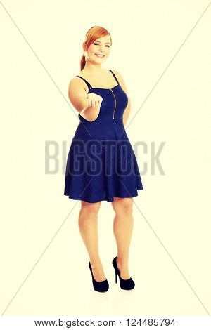 Overweight woman presenting something