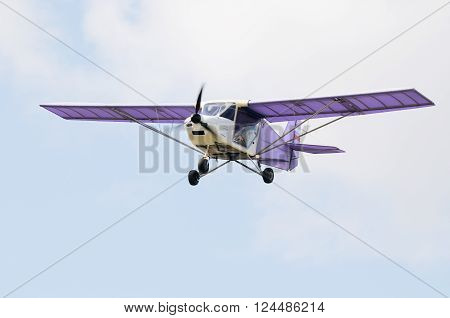 Private propeller-driven airplane flying in cloud sky
