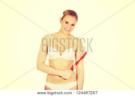 Woman holding red huge toothbrush