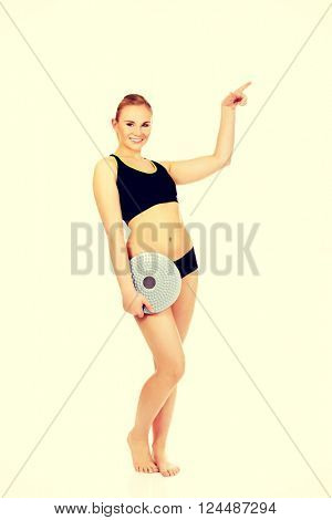 Young athletic woman holding balance board and pointing for copyspace or something