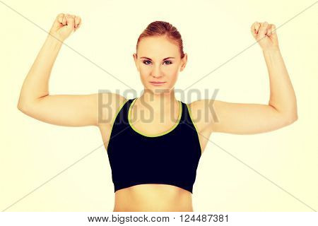 Young athletic woman showing muscles