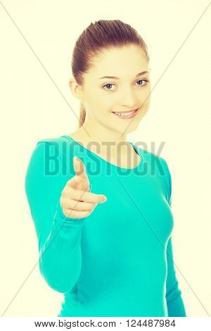 Smiling young woman pointing on you.
