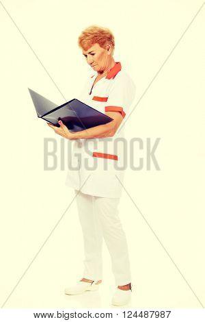 Elderly female doctor or nurse holds black binder and reads
