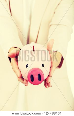 Elderly woman holding piggy bank