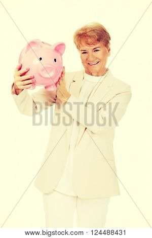 Smile elderly woman holding piggy bank