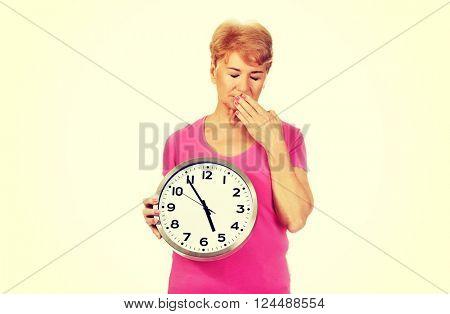 Elderly yawning woman holding big clock