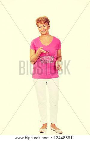 Senior smiling woman holding mini shopping basket