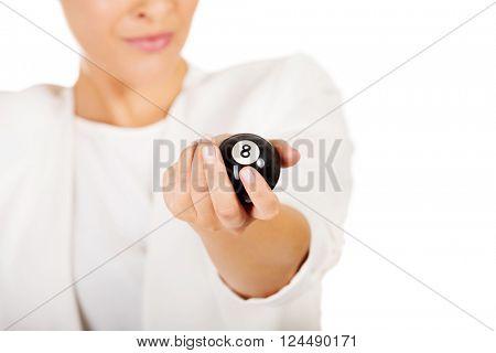 Happy businesswoman holding eight billiard ball