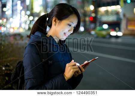 Woman read messag on cellphone at street in Tokyo city