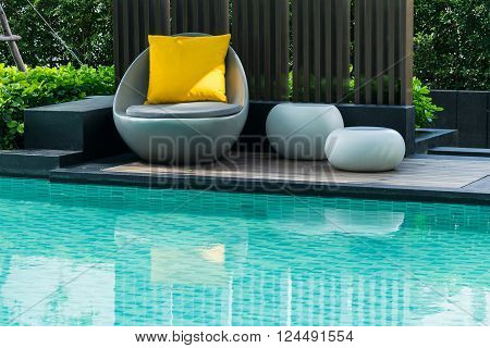 Relaxing chairs with pillows beside swimming pool