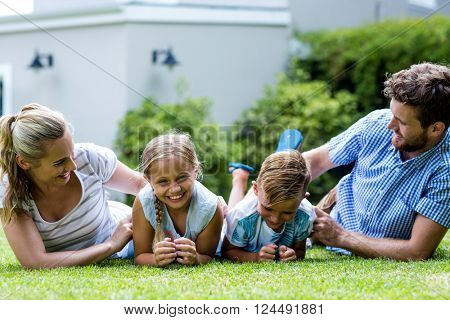 Happy parents tickling children while lying on grass in yard