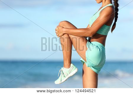 Fitness runner body closeup doing warm-up routine on beach before running, stretching leg muscles with standing single knee to chest stretch. Female athlete preparing legs for cardio workout.