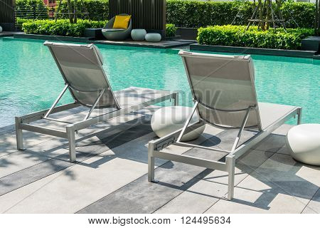 Swimming pool with beach chairs on pool deck